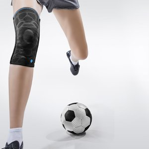 A person with knee pads tries to kick a ball.