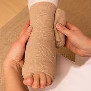 Compression bandages are applied to a foot.
