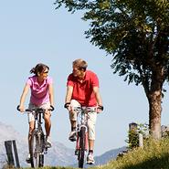 A couple ride their bikes outside.