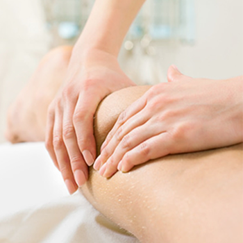 A doctor treats a patient using manual lymphatic drainage.