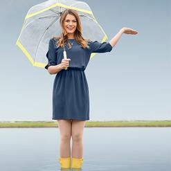 A woman stands beneath an umbrella.