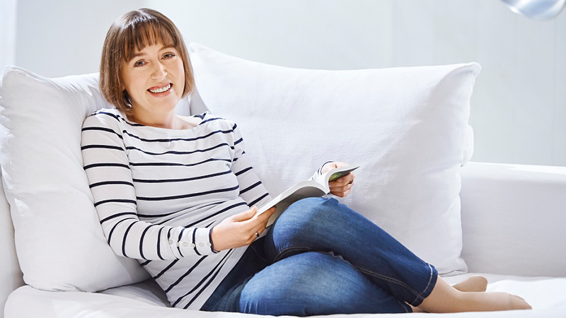 Frau auf Sofa mit Lastofa Kompressionsstrümpfen von Ofa Bamberg