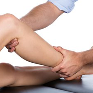 A physiotherapist massages a patient's leg.